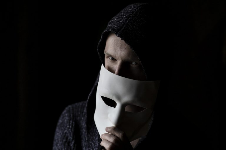 The suspicious man with a mask on the face